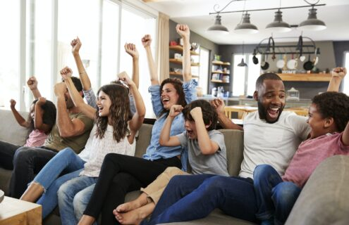 Two Families Watching Sports On Television And Cheering